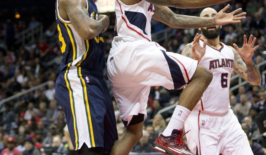 Atlanta Hawks guard Jeff Teague (0) goes up for a basket as Utah Jazz forward Trevor Booker (33) defends during the first half of an NBA basketball game Wednesday, Nov. 12, 2014, in Atlanta. (AP Photo/John Bazemore)