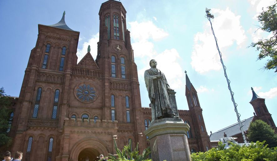 FILE - In this July 29, 2013 file photo, the statue of Joseph Henry stands outside the headquarters of the Smithsonian Institution on the National Mall in Washington. he Smithsonian Institution plans to give its buildings and gardens alongside the south side of the National Mall a facelift, adding entrances and refurbishing the Smithsonian Castle. (AP Photo/J. Scott Applewhite, File)
