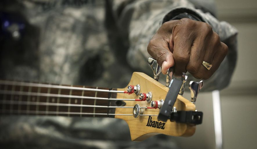 ADVANCE FOR USE MONDAY, NOV. 17 - In this photo taken Wednesday, Nov. 5, 2014, Spc. Richard Telford tunes a bass guitar  during a Warrior Cry Music Project music class in San Antonio, Texas.  The project is a national nonprofit based in San Antonio that offers music therapy to wounded warriors.  (AP Photo/San Antonio Express-News, Bob Owen) RUMBO DE SAN ANTONIO OUT; NO SALES, MAGS OUT