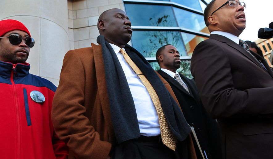 Michael Brown family attorneys Anthony Gray, right, and Benjamin Crump join Michael Brown's stepfather Louis Head, left, at a news conference in front of the Buzz Westfall Justice Center in Clayton, Mo., on Thursday, Nov. 13, 2014. Attorneys for the family of Michael Brown are urging restraint by both protesters and police once a grand jury decides whether the suburban St. Louis officer who shot him should face charges. (AP Photo/St. Louis Post-Dispatch, Robert Cohen)  EDWARDSVILLE INTELLIGENCER OUT; THE ALTON TELEGRAPH OUT