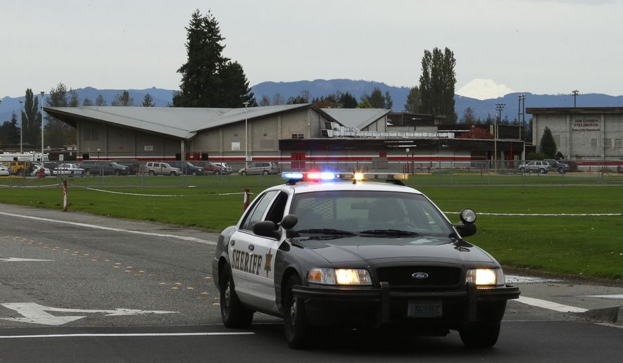 FILE - In this photo taken Oct. 24, 2014, a sheriff's vehicle sits parked in the driveway of Marysville Pilchuck High School in Marysville, Wash., the afternoon after a shooting in the school's cafeteria. On Wednesday, Nov. 12, 2014, authorities released the 911 calls from students, parents, neighbors, school workers and teacher Megan Silberberger, who tried to intervene when a freshman student, Jaylen Fryberg, opened fire at a group of friends at the school. (AP Photo/Ted S. Warren, file)