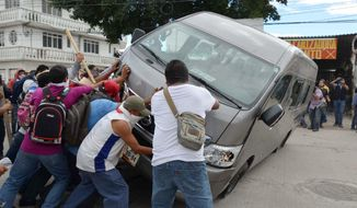 Teachers flip a vehicle during a clash with riot police in Chilpancingo, Mexico, Tuesday, Nov. 11, 2014. Supporters of the missing 43 college rural students, refusing to believe they are dead, have kept up the protests that have blocked major highways and set government buildings ablaze in recent weeks. The students disappeared at the hands of a city police force on Sept. 26 in the town of Iguala. (AP Photo/Alejandrino Gonzalez)