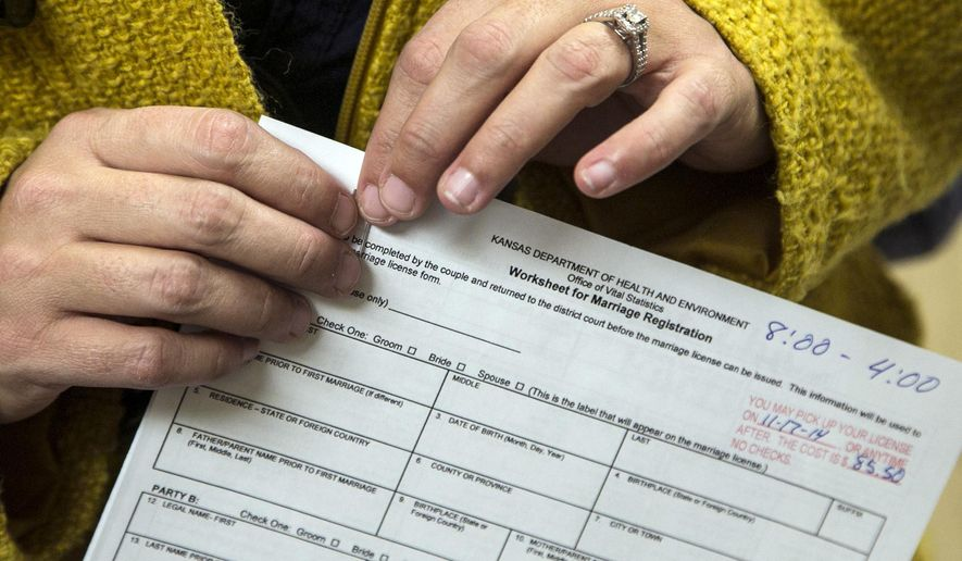 A woman holds an application for a marriage license at the Sedgwick County Courthouse in Wichita, Kan.,Thursday Nov. 13, 2014.  The U.S. Supreme Court denied a request Wednesday from the state to block gay and lesbian couples from getting married in Kansas while the state fights lawsuits challenging Kansas' gay-marriage ban. (AP Photo/The Wichita Eagle, Mike Hutmacher)