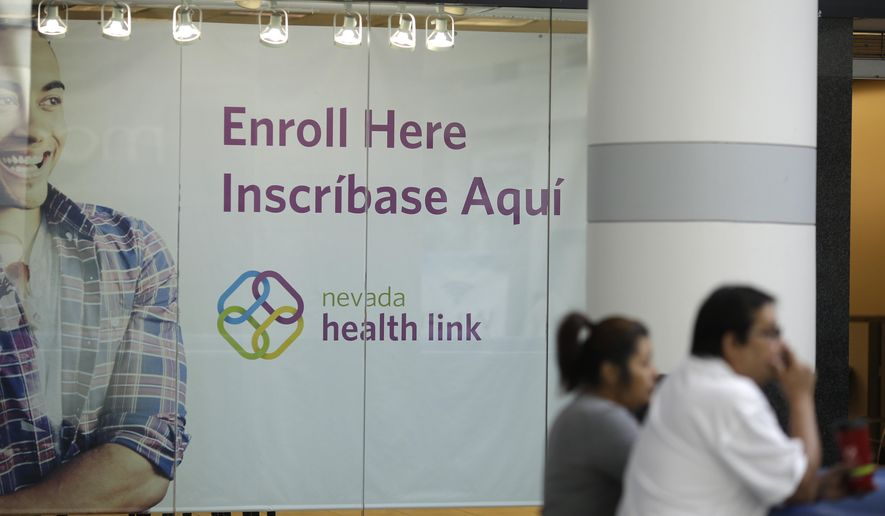 People stand near an insurance store for Nevada Health Link at the Boulevard Mall Thursday, Nov. 13, 2014, in Las Vegas. Nevada is preparing to open up its revamped health exchange site for another round of enrollments. The store will be open for business Saturday. (AP Photo/John Locher)