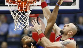Washington Wizards center Marcin Gortat (4), from Poland, dunks over Detroit Pistons forward Greg Monroe (10) during the first half of an NBA basketball game, Wednesday, Nov. 12, 2014, in Washington. (AP Photo/Alex Brandon)