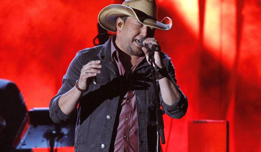 "FILE - In this Nov. 5, 2014 file photo, Jason Aldean performs onstage at the 48th annual CMA Awards at the Bridgestone Arena in Nashville, Tenn. Aldean joined Taylor Swift and others artists who have decided to remove their music from Spotify, which allows users to stream albums for free. The album has sold more than 467,000 copies since its release on Oct. 7 and hit No. 1 on the Billboard 200 chart. ""Old Boots, New Dirt"" also had the biggest first week for a country album on Spotify with more than 3 million streams. (Photo by Wade Payne/Invision/AP, File)"