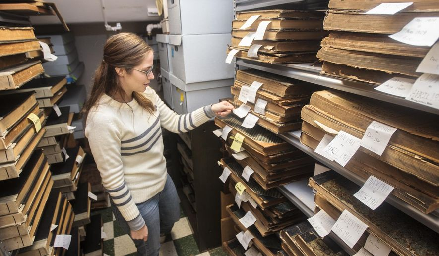 """In this Nov. 11, 2014 photo, Maddie Lundy, executive director of The History Center of Traverse City, shows the newspaper collection maintained at the center's 322 6th St. location in Traverse City, Mich. The center will remain closed and maintain staff hours at a """"bare minimum"""" until it finds another location or solution for a lease that's set to expire, executive director Maddie Lundy told the Traverse City Record-Eagle. (AP Photo/The Record-Eagle, Pete Rodman)  MANDATORY CREDIT"""