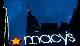 In this Nov. 21, 2013, photo, with the Empire State building in the background, the Macy's logo is illuminated on the front of the department store in New York. (AP Photo/Mark Lennihan) ** FILE **