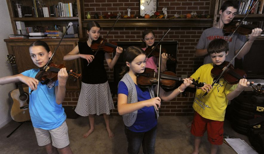 ADVANCE FOR USE MONDAY, NOV. 17 - IN this photo taken on Oct. 6, 2014,  the members of the Earthman Family Fiddlers rehearse at their home in Knox City, Texas. The Earthman Family Fiddlers play shows around their area of the Big Country. (AP Photo/The Abilene Reporter-News, Ronald W. Erdrich) MANDATORY CREDIT