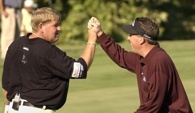 John Daly, left, high fives with teammate Phil  Mickelson after Mickelson birdied the third hole to put their team up against Tiger Woods and Hank Kuehne at the Battle At the Bridges Monday Aug. 2, 2004 in San Diego. (AP Photo/Denis Poroy)