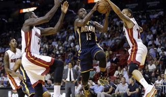 Indiana Pacers' Donald Sloan (15) shoots as Miami Heat's James Ennis, left, and Shabazz Napier (13) defend in the first half of an NBA basketball game, Wednesday, Nov. 12, 2014, in Miami. (AP Photo/Lynne Sladky)