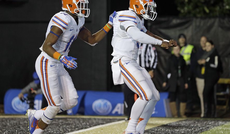 Florida quarterback Treon Harris, right, celebrates with wide receiver Demarcus Robinson, left, after Harris scored a touchdown on a 7-yard run against Vanderbilt in the fourth quarter of an NCAA college football game Saturday, Nov. 8, 2014, in Nashville, Tenn. Florida won 34-10. (AP Photo/Mark Humphrey)