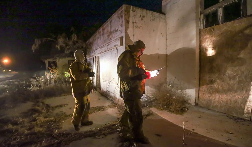 Argonia firefighters Justin Stringer, right, and John Layton check for structural damage to buildings in Milan, Kansas after a nearby 4.8 earthquake struck the area Wednesday, Nov. 12, 2014. (AP Photo/The Wichita Eagle - Kansas.com, Fernando Salazar)