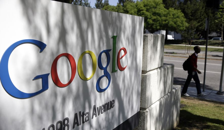 A man walks past a Google sign at the company's headquarters in Mountain View, Calif., in this June 5, 2014, file photo. (AP Photo/Marcio Jose Sanchez, File)