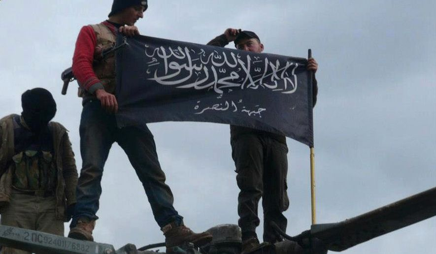 FILE - In this Friday, Jan. 11, 2013 file citizen journalism image provided by Edlib News Network, ENN, which has been authenticated based on its contents and other AP reporting, rebels from al-Qaida-affiliated Jabhat al-Nusra, also known as the Nusra Front, wave their brigade flag, as they step on the top of a Syrian air force helicopter at Taftanaz air base that was captured by the rebels in Idlib province, northern Syria. In the early dawn of Nov. 2, militant leaders with the Islamic State group and al-Qaida gathered at a farm house in northern Syria and sealed a deal to stop fighting each other and work together against their opponents, a prominent Syrian opposition official and a rebel commander said. Such an alliance could be a significant blow to struggling U.S-backed Syrian rebels. (AP Photo/Edlib News Network ENN, File)