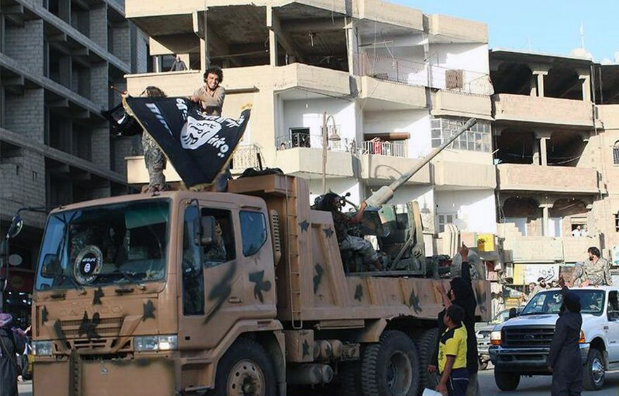 In this undated file image posted by the Raqqa Media Center, a Syrian opposition group, on Monday, June 30, 2014, which has been verified and is consistent with other AP reporting, fighters from the al Qaeda-linked Islamic State group parade in Raqqa, Syria. (AP Photo/Raqqa Media Center of the Islamic State group, File)