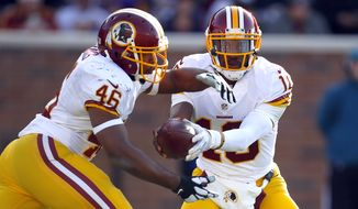 Washington Redskins quarterback Robert Griffin III (10) hands the ball off the running back Alfred Morris (46)l against the Minnesota Vikings during an NFL football game, Sunday, Nov. 2, 2014, in Minneapolis. (Jeff Haynes/AP Images for Panini)