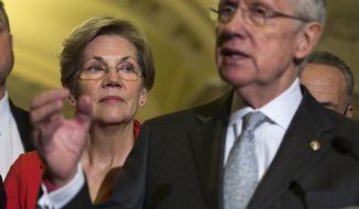 Sen. Elizabeth Warren, Massachusetts Democrat, listens at left as Senate Majority Leader Harry Reid of Nevada speaks during a news conference Thursday on Capitol Hill. (Associated Press)