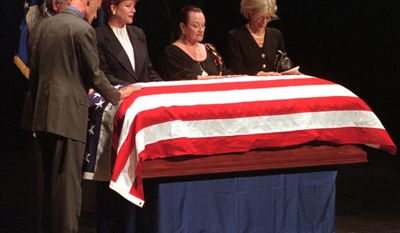 From left, Barry Goldwater Jr., son, Bob Goldwater, brother, Peggy Clay, daughter, Joanne Goldwater, daughter and Susan Goldwater, widow of the late U.S. Senator Barry Goldwater place their hands on his casket Wednesday, June 3, 1998, as they resite the Lords Prayer during funeral services at Gammage auditorium at Arizona State University.  (AP Photo/Jeff Robbins)