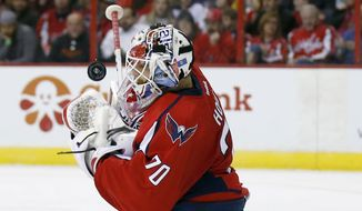Washington Capitals goalie Braden Holtby (70) bobbles the puck as he blocks a shot in the second period of an NHL hockey game against the New Jersey Devils, Friday, Nov. 14, 2014, in Washington. (AP Photo/Alex Brandon)