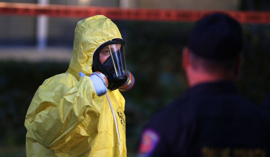 A hazmat worker looks up while finishing up cleaning outside an apartment building of a hospital worker Oct. 12 in Dallas. (Associated Press)