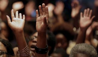 In this Aug. 17, 2014 file photo, people raise their hands during a rally at Greater Grace Church for Michael Brown, who was killed by police, last Saturday in Ferguson, Mo. (AP Photo/Charlie Riedel, File) ** FILE **