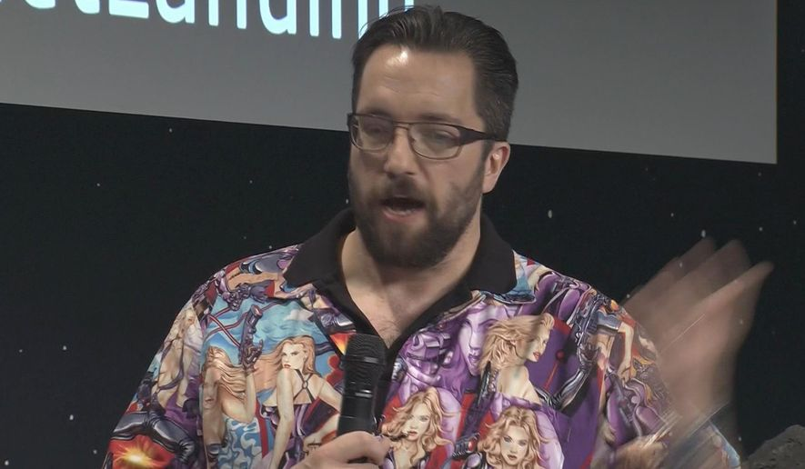 """In this image issued from ESA, showing British physicist Matt Taylor Thursday Nov. 13, 2014, sporting a garish bowling shirt featuring a collage of pin-up girls in various states of undress, during an interview at the satellite control centre of the European Space Agency (ESA) in Darmstadt, Germany, on Thursday Nov. 13, 2014. On Friday Nov 14, Taylor offered an unsolicited apology about his shirt """"I made a big mistake and I offended many people,"""" he said. """"And I'm very sorry about this."""" (AP Photo/ESA) TV OUT - NO SALES"""