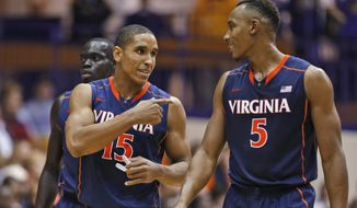 Virginia guard Malcolm Brogdon (15) talks with forward Darion Atkins (5) during the second half of an NCAA college basketball game  against James Madison in Harrisonburg, Va., Friday, Nov. 14, 2014. Virginia won 79-51. (AP Photo/Steve Helber)