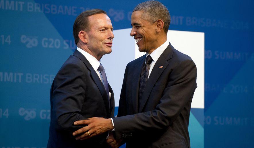 U.S. President Barack Obama, right, is welcomed by Australia's Prime Minister Tony Abbott upon arrival for the G20 Summit in Brisbane, Australia Saturday, Nov. 15, 2014. (AP Photo/Alain Jocard, Pool)
