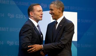 U.S. President Barack Obama, right, is welcomed by Australia's Prime Minister Tony Abbott upon arrival for the G20 Summit in Brisbane, Australia Saturday, Nov. 15, 2014. (AP Photo/Alain Jocard, Pool)