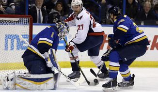 Washington Capitals' Karl Alzner, center, reaches for a puck as St. Louis Blues goalie Brian Elliott, left, and Kevin Shattenkirk defend during the first period of an NHL hockey game Saturday, Nov. 15, 2014, in St. Louis. (AP Photo/Jeff Roberson)