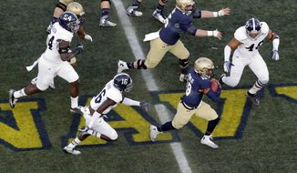 Navy quarterback Keenan Reynolds, bottom right, runs past Georgia Southern defenders for a first down in the first half of an NCAA college football game, Saturday, Nov. 15, 2014, in Annapolis, Md. (AP Photo/Patrick Semansky)