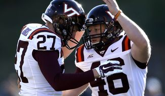 Virginia Tech kicker Joey Slye (46) is congratulated by A.J. Hughes (27) following Slye's field-goal against Duke during the second half of an NCAA college football game in Durham, N.C., Saturday, Nov. 15, 2014. Virginia Tech won 17-16. (AP Photo/Gerry Broome)