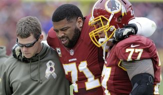 Washington Redskins tackle Trent Williams (71) is helped off the field after an injury during the first half of an NFL football game against the Tampa Bay Buccaneers in Landover, Md., Sunday, Nov. 16, 2014. (AP Photo/Patrick Semansky)