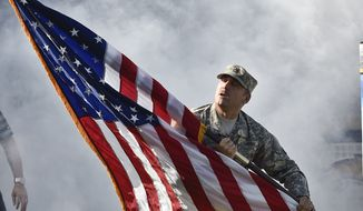 A soldier races on the field with the American flag as part of the salute to service pregame activities at the NFL football game between the San Diego Chargers and against the Oakland Raiders Sunday, Nov. 16, 2014, in San Diego. (AP Photo/Denis Poroy)