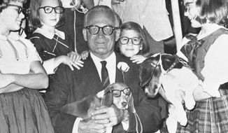 Youngsters in signature Goldwater glasses carry beagles to greet Sen. Barry Goldwater during a campaign stop in Montgomery, Alabama. (associated press)
