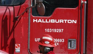 An unidentified worker passes a truck owned by Halliburton at a remote site for natural-gas producer Williams in Rulison, Colo., April 15, 2009. (Associated Press) ** FILE **
