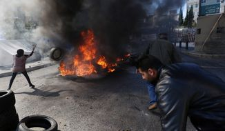 Relatives of Lebanese soldiers held hostage by Islamic militants burn tires, during a demonstration to demand action to secure the captives' release, in front of the government headquarters in downtown Beirut, Lebanon, Monday, Nov. 17, 2014. The militants, including the al Qaeda linked Nusra Front and the extremist Islamic State group, are holding some 20 Lebanese soldiers and policemen hostages since August, when they briefly overran a Lebanese border town. (AP Photo/Bilal Hussein)