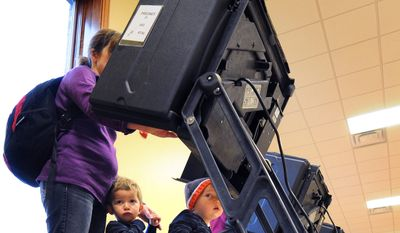 """Jackson, left, and Jacob Sanchez, 2, wait while their mother, Jana Sanchez, votes on Election Day, Tuesday, Nov. 4, 2014, in Salina, Kan. Sanchez said she wasn't sure how bringing her two year old sons with her to vote would go, """"but it was fun."""" (AP Photo/Salina Journal, Tom Dorsey)"""