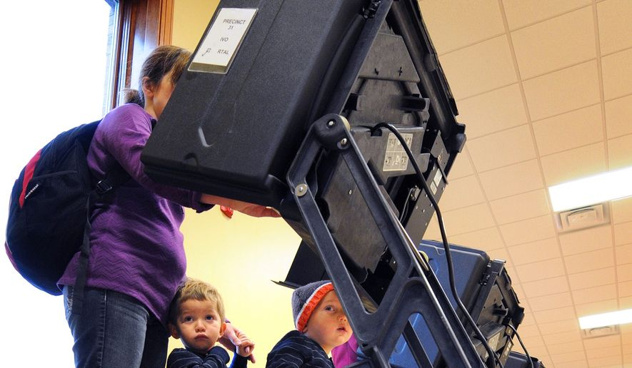"Jackson, left, and Jacob Sanchez, 2, wait while their mother, Jana Sanchez, votes on Election Day, Tuesday, Nov. 4, 2014, in Salina, Kan. Sanchez said she wasn't sure how bringing her two year old sons with her to vote would go, ""but it was fun."" (AP Photo/Salina Journal, Tom Dorsey)"