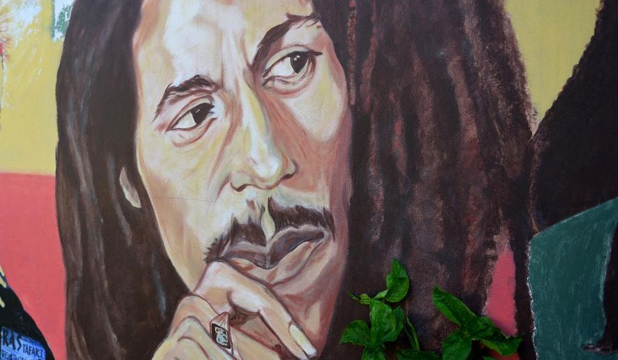 """In this Feb. 6, 2013, file photo, a mural depicting reggae music icon Bob Marley decorates a wall in the yard of Marley's Kingston home in Jamaica. A U.S. private equity firm announced Tuesday, Nov. 18, 2014 it has joined the family of late reggae star Bob Marley in hopes of building what it touts as the """"world's first global cannabis brand."""" (AP Photo/ David McFadden, File)"""