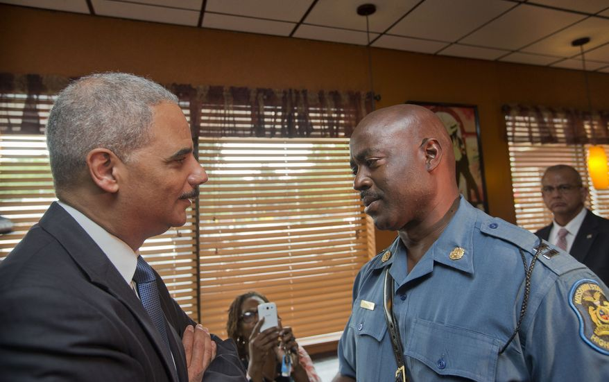 FILE - In this Aug. 20, 2014 file-pool photo, Attorney General Eric Holder speaks with Capt. Ron Johnson of the Missouri State Highway Patrol at Drake's Place Restaurant in Ferguson, Mo. As local authorities in Missouri near the end of their investigation into the Ferguson shooting, a separate, ongoing federal civil rights review of the entire police department holds the greater potential to refashion the agency and spur long-lasting change, experts say. The Justice Department, which is investigating the Aug. 9 shooting of 18-year-old Michael Brown along with a county grand jury, is more than two months into its probe of the Ferguson department's practices. The civil rights inquiry, relying on data and interviews, is searching for any pattern of racial bias in how officers in the predominantly white department interact with the majority-black community.   (AP Photo/Pablo Martinez Monsivais, File-Pool)