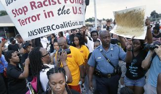 Missouri Highway Patrol Capt. Ron Johnson, center right, walks among people protesting the police shooting death of Michael Brown in Ferguson, Mo. Emails sent to top public-safety officials both criticizing and praising Johnson for appearing to sympathize with protesters illustrate one of the challenges that authorities could face after a grand jury decides whether to charge the police officer who killed Brown _ how to walk a fine line between providing public empathy and security. (AP Photo/Charlie Riedel, File)