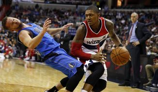 Dallas Mavericks guard J.J. Barea, left, reacts after a foul by Washington Wizards guard Bradley Beal during the second half of an NBA basketball game, Wednesday, Nov. 19, 2014, in Washington.  The Mavericks won 105-102. (AP Photo/Alex Brandon)