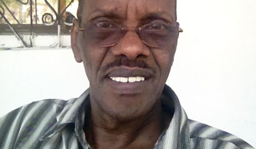 This photo taken Sunday, Sept. 29, 2013 and provided by the family of Abdullahi Ali Anshur, 60, shows the Somali-American from Minnesota at his office in Mogadishu, Somalia.  Gunmen shot and killed Abdullahi Ali Anshur, an engineer from Minnesota who had left a well-paying job in the U.S to help the fledgling Mogadishu city government with urban planning and drainage systems, a Somali official and relative said Wednesday, Nov. 19, 2014. (AP Photo/Family of Abdullahi Ali Anshur)