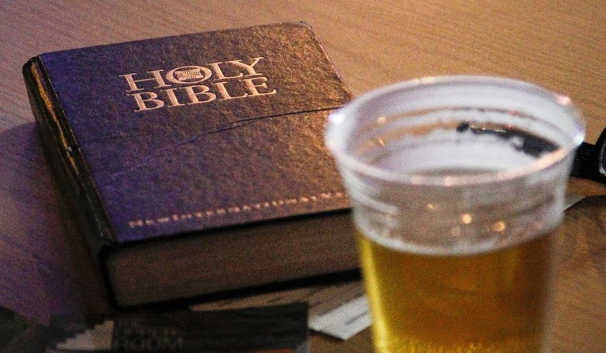 In a photo from Nov. 11, 2014, a Bible is seen on a table with a beer at The Loft in downtown Lansing, Mich. More than 60 people gathered at The Loft in downtown Lansing, Mich., for the premiere of Crossroads Church's weekly gathering. This wasn't a church but a bar. Because they want people to come whose relationship with church is tenuous or non-existent, the pastors have promised to buy a drink for every first-timer.(AP Photo/Lansing State Journal, Matthew Dae Smith)