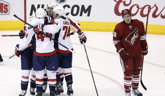Washington Capitals' Eric Fehr, top, smiles as he celebrates his game-winning goal against the Arizona Coyotes with teammates Brooks Orpik (44), John Carlson (74) and Troy Brouwer, left, as Coyotes' Michael Stone (26) skates away during overtime of an NHL hockey game Tuesday, Nov. 18, 2014, in Glendale, Ariz. The Capitals defeated the Coyotes 2-1. (AP Photo/Ross D. Franklin)