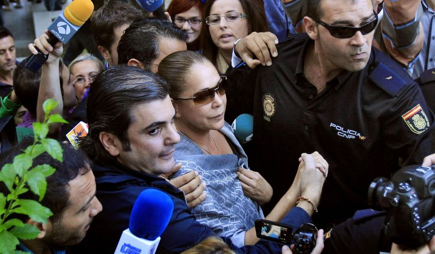 """FILE - In this Oct. 14, 2010 file photo, a police officer escorts Spanish singer Isabel Pantoja, center, as she arrives at the court in Marbella, southern Spain. A Spanish court has ordered popular Spanish folk singer Isabel Pantoja to jail after her appeals against a two-year conviction for money laundering were rejected, giving Pantoja, 58, three days to enter prison as of Wednesday. Pantoja was also fined euro1.2 million ($1.5 million) following the 2012 trial. Pantoja is a fixture in Spain's gossip magazines and TV shows. She was married to the famous bullfighter Francisco """"Paquirri"""" Rivera, who died in the bullring in 1984. (AP Photo/Sergio Torres, File)"""