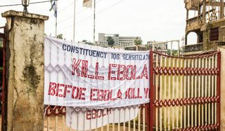 FILE- This Sept. 14, 2014, file photo shows a sign reading 'Kill Ebola Before Ebola Kill You', on a gate as part of the country's Ebola awareness campaign in the city of  Freetown, Sierra Leone. The government's worst-case scenario forecast for the Ebola epidemic in West Africa won't happen, a U.S. health official said Wednesday, Nov. 19, 2014. (AP Photo/ Michael Duff, File)