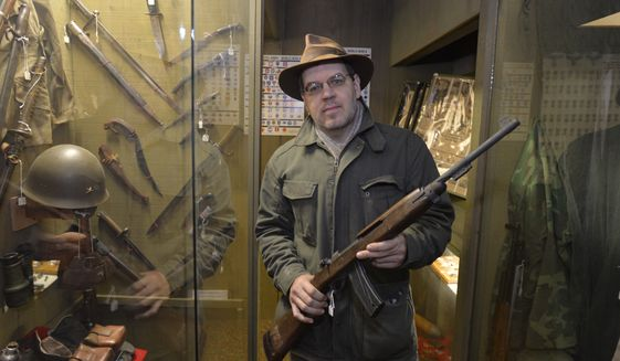 In this photo taken on Tuesday, Nov. 18, 2014, Lynden Museum director and curator Troy Loginbill, holds a Korean War M1  on loan to the Lynden, Wash., museum. The museum has decided to return the M1 carbine and ten other loaned weapons to their owners to comply with the new gun registration law Initiative 594. (AP Photo/The Bellingham Herald, Philip A. Dwyer)